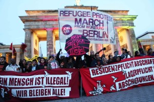 Refugee strike activists pose in front of Brandenburg Gate, Berlin Source: Deutschhilde, Creative Commons