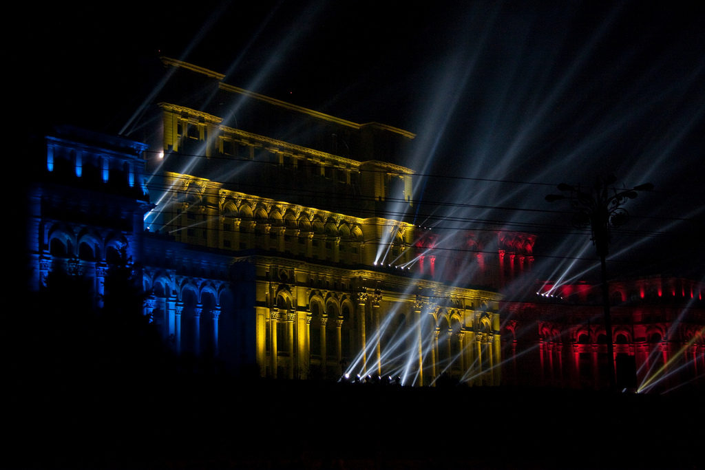 The huge Romanian Parliament Palace beautifully lit in the national flag colors red, yellow and blue during a New Year's outdoors celebration. Some large lasers get projected onto the dark sky. Source: Horia Varlan, Creative Commons